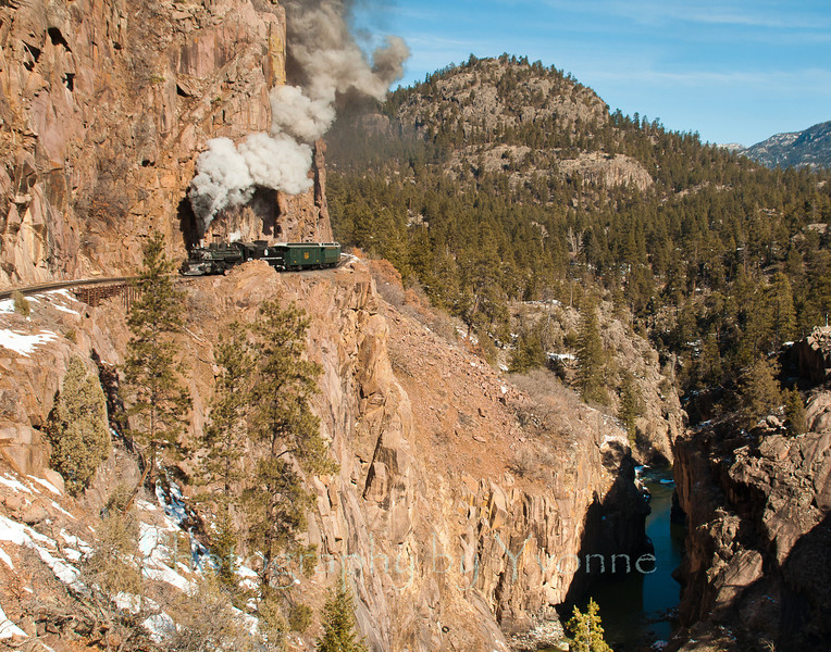 A southbound train travels along the shelf track high above the Animas River.