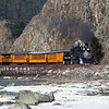 Winter Train steams southbound in front of granite cliffs.