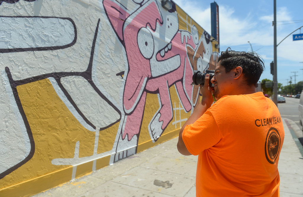 . Nash Jacquez photographs a mural in the Cambodia Town section of Long Beach on Tuesday, July 18, 2017. Artist Jason Keam painted this mural at 1601 East Anaheim St . The Cambodia Town Mural Project has had artists put up eight murals on buildings in the Anaheim Street corridor. (Photo by Scott Varley, Press-Telegram/SCNG)