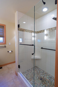 A simple, but elegant shower with cubby for shampoo, grab bars, drilled towel bar on the pivoting door, and corner foot step.