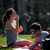 Springtime on University of Rochester River Campus: students Sophie Esquier of Rochester (L) blows bubbles as John DeCourcey of Boston reads on  Eastman Quad March 20, 2012. // photo by J. Adam Fenster / University of Rochester