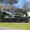 Heisler #6 and Shay #11 pull a log train past the former Pocahontas Supply Co. general store.