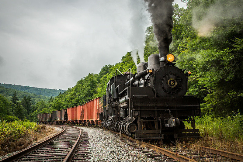 "Black Diamonds and Irony: This image shows Cass's legendary Western Maryland Shay No. 6, coupled to a cut of coal hoppers alongside the former lumbering town of Spruce, West Virginia. 85 years ago, the sounds of whirring sawblades and steam exhaust echoed throughout this valley. One of workaday Shays assigned to this line was a 150 ton behemoth, the Greenbrier Cheat & Elk's No. 14. By the end of the roaring twenties, the rails at Spruce were sold to the Western Maryland Rwy and No. 14 was deemed surplus. At the height of the Great Depression, the No. 14 found its way to a new railroad, hauling coal for the WM in Maryland. In 1942, the engine was involved in a runaway accident, placing the then renumbered Western Maryland No. 5 out of service. To keep up with wartime coal demand, Western Maryland ordered a new Shay from Lima. No. 6 arrived on property in May of 1945 and hauled coal hoppers for four short years, before retirement. Through an amazing tale of preservation, the very locomotive built to replace her wrecked sister now plies old No. 14's ""home"" rails on the former GC&E at Spruce. Though the mills are silent, steam still echoes through this lush valley."