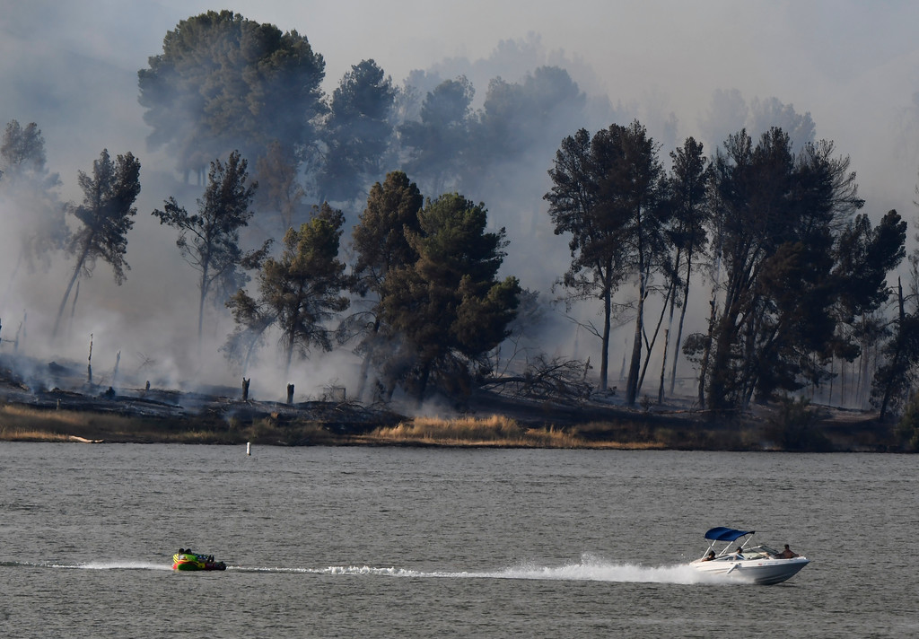 . June 17,2017. Caustic Lake. CA. People continue to enjoy the boating on the lake as  LA county and LA city firefighters do mostly of air attack on a brush fire near Lake Castaic  Saturday. The fire rapidly has grown to 550 acres as of 4 p.m.  A total of 195 firefighters from the Los Angeles County Fire Department, plus firefighters from the Angeles National Forest, battled the blaze.  As of 4 p.m., there was no containment line and no mandatory evacuations of the area,  Photo by Gene Blevins/LA DailyNews/SCNG
