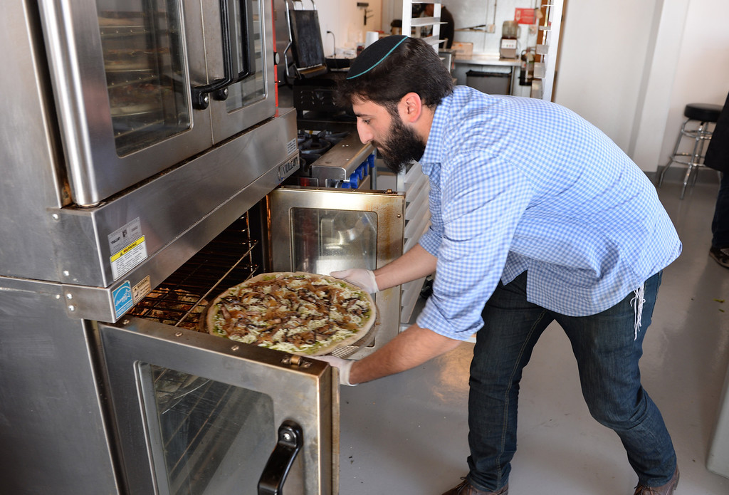 . Levi Chayo slides a pizza into the oven. Chayo Eatery in Torrance is a kosher restaurant filling a niche in the local Jewish community. They make fresh pizzas, salads, soups and sandwiches. Photo by Brad Graverson/The Daily Breeze 01/03/14