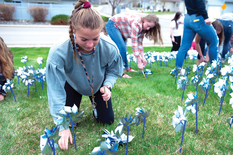 Matthew Gaston | The Sheridan Press<br>Talia Steele helps place pinwheels in the lawn at Sheridan High School to raise awareness for child abuse Wednesday, April 24, 2019. Sheridan High School students partnered with Big Brothers Big Sisters for this event.