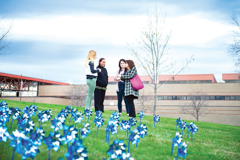Matthew Gaston | The Sheridan Press<br>From left, Nichole Johnson; a Sheridan High School junior, Linnae Taylor; Big Brothers and Big Sisters case manager, Skylar Scott; a University of Wyoming graduate student and Sandy Thiel; director of community engagement for Big Brothers and Big Sisters organized the planting of pinwheels in the lawn at Sheridan High School to raise awareness for child abuse prevention Wednesday, April 24, 2019.