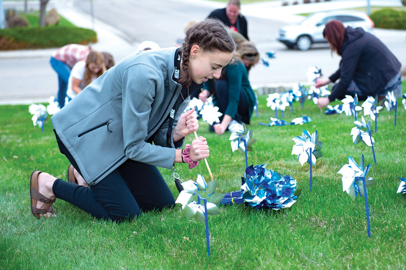 Matthew Gaston | The Sheridan Press<br>Sophmore Payton Rott uses a dowell rod to make holes for planting pinwheels in the lawn at Sheridan High School Wednesday, April 24, 2019. Sheridan students and Big Brothers Big Sisters are planting pinwheels to raise awareness for child abuse prevention.