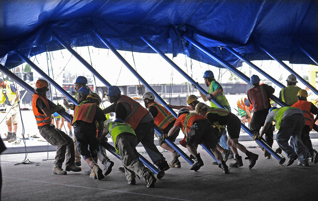 ". Workers push up the last poles of the main Cirque du Soleil bigtop tent where the circus is setting up for its performance of ""Totem\"" starting Oct. 11. Set up is near the Lane Victory at berth 45. (Oct 2, 2013. Photo by Brad Graverson/The Daily Breeze)"