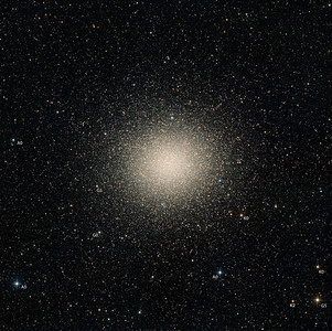 """Omega Centauri. The stars of omega are mostly extremely old, and cooler than the sun. This, combined with reddening due to dust, should produce a general pastel orange appearance. To help you interpret the image, we have labelled several stars with their spectral types. We have chosen to represent the G0 star at 8 o'clock a pale yellow. A close look at the core shows many """"blue stragglers"""". There are a smattering of brighter red giants most noticeable further out from the core. There is an edge-on galaxy toward top left of field. The cluster seems not to be a perfect ball, but seems to show fat fingers of stars radiating far outward.  Nine panel mosaic. Total exposure 12 hrs in 10 minute subs. Aspen CG16M on 20"""" PlaneWave. Full moon. Field 1.08 degrees wide, North up. 0.55 sec arc per pixel."""