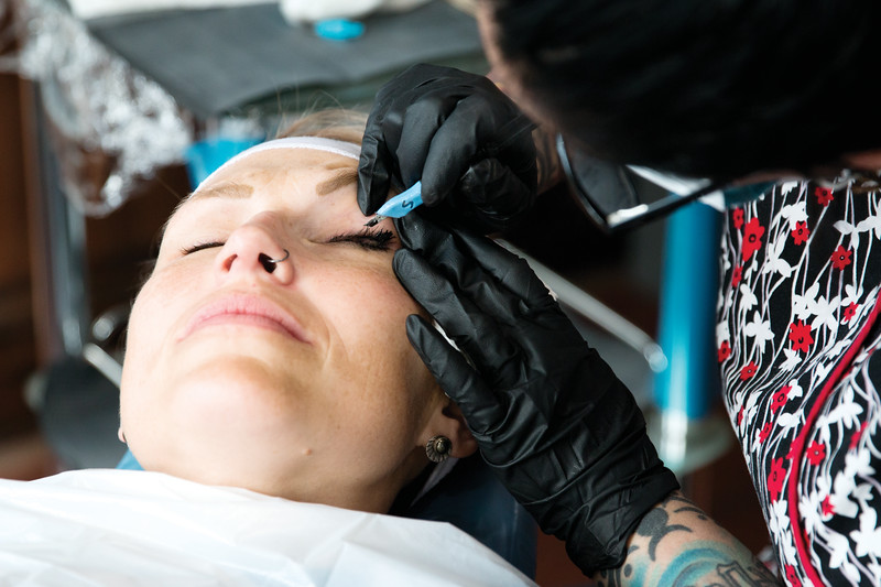 Matthew Gaston | The Sheridan Press<br>Paige Pozos makes the final pass on Kyan Sanderson's left eye, ensuring that there are no inconsistencies on the eye lash enhancement Friday, Oct. 19, 2018.