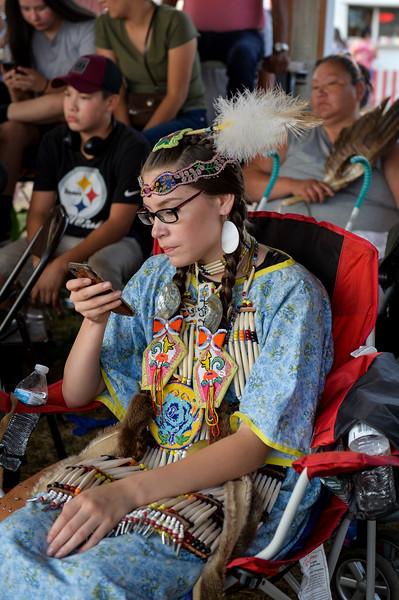 Ashleigh Fox | The Sheridan Press<br /> Shaydon Standing Rock of Rocky Boy, Montana, checks her phone before dancing at the 100th Crow Fair Friday, Aug. 17, 2018.