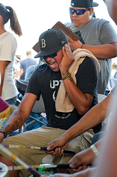 Ashleigh Fox | The Sheridan Press<br /> A member of the Crow Agency drum circle, Night Hawk Jrz, sings while a judge stands behind during the 2018 Crow Fair competition Friday, Aug. 17, 2018.
