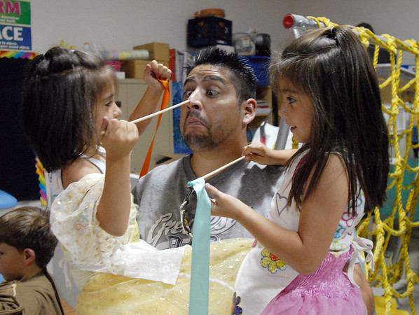 """D.J. Ruybal reacts his 5 year old twin daughters Serena, left, and Charlize show him their wands after the performance of Broomfield Academy Summer Camp's play """"The Emperor's News Clothes"""".<br /> <br /> June 18, 2010<br /> Staff photo/ David R. Jennings"""