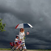 Madelynn Rarimi, 3, with her mother, Heather, rides in the bike parade  as storm clouds form behind at Broomfield's Great American Picnic at Broomfield County Commons.  The fireworks show was canceled due to the severe weather.<br /> <br /> <br /> July 4, 2010<br /> Staff photo/ David R. Jennings
