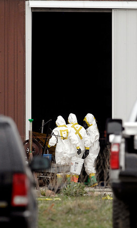 Investigators dressed in hazmat suits work enter one of the barns Wednesday where  the remains of as many as 100 animals were found dead Tuesday night at a farm on County Road 1700 North near 350 West.