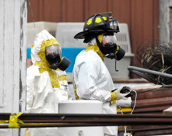 Investigators dressed in hazmat suits work around one of the barns Wednesday where  the remains of as many as 100 animals were found dead Tuesday night at a farm on County Road 1700 North near 350 West.