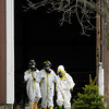 Investigators dressed in hazmat suits exit one of the barns Wednesday where  the remains of as many as 100 animals were found dead Tuesday night at a farm on County Road 1700 North near 350 West.