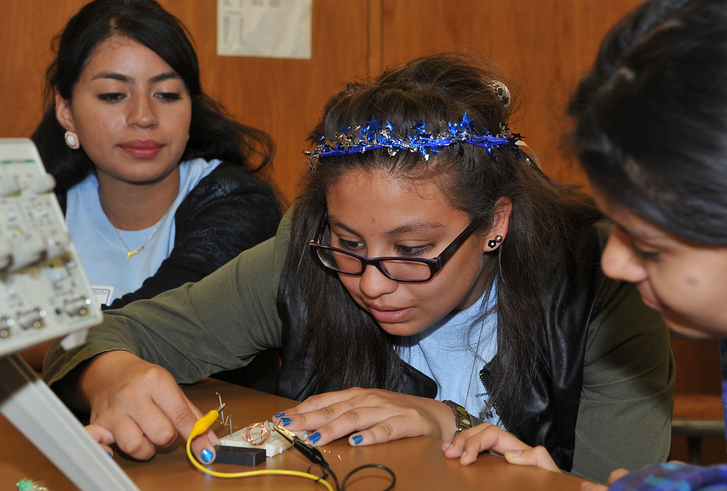 . 10/4/13 - L-R Jennifer Flameno, Rebecca Fuentes and Monica Banks try to create a paperclip direct current motors during a workshop on Friday morning. Some 200 middle school and high school girls from school districts in Long Beach, Montebello and Paramount will take part in Cal State Long Beach�s �Women Engineers at The Beach,� a program developed to inspire young girls to consider careers in engineering, technology and computer science. (Photo by Brittany Murray/Press Telegram)