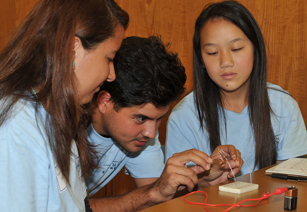 . 10/4/13 - L-R Janhete Diaz, third year engineer student Samuel Lopez and Shayna Lee try to create a paperclip direct current motors during a workshop on Friday morning. Some 200 middle school and high school girls from school districts in Long Beach, Montebello and Paramount will take part in Cal State Long Beach�s �Women Engineers at The Beach,� a program developed to inspire young girls to consider careers in engineering, technology and computer science. (Photo by Brittany Murray/Press Telegram)