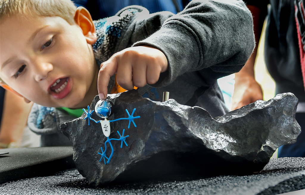 . Jesse Quezada of San Gabriel, placed a space monster toy, to a meteorite that is magnet because of its iron content.  The Gibeon Meteorite came from Great Namnaland Nambia in 1836.  Outdoor space expo, took place at Caltech\'s Beckman Auditorium Mall Saturday, May 9, 2015. Visitors took  a tour of our solar system, with booths featuring NASA missions, and learn how NASA communicates spacecraft beyond Earth orbit. (Photo by Walt Mancini/Pasadena Star-News)