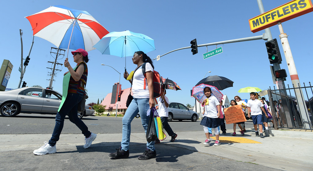 . Parents  and students from Roosevelt Elementary School march along Lemon Avenue and Pacific Coast Highway,  to voice their concerns about having their children walk four miles roundtrip to and from school now that Roosevelt is under construction. The students have been displaced from their original campus and now have to walk longer than they did to and from school as a result. Students and their families want Long Beach Unified to provide buses for their children, but so far LBUSD hasn\'t complied. Long Beach Calif., Thursday June 5,  2014.     (Photo by Stephen Carr / Daily Breeze)