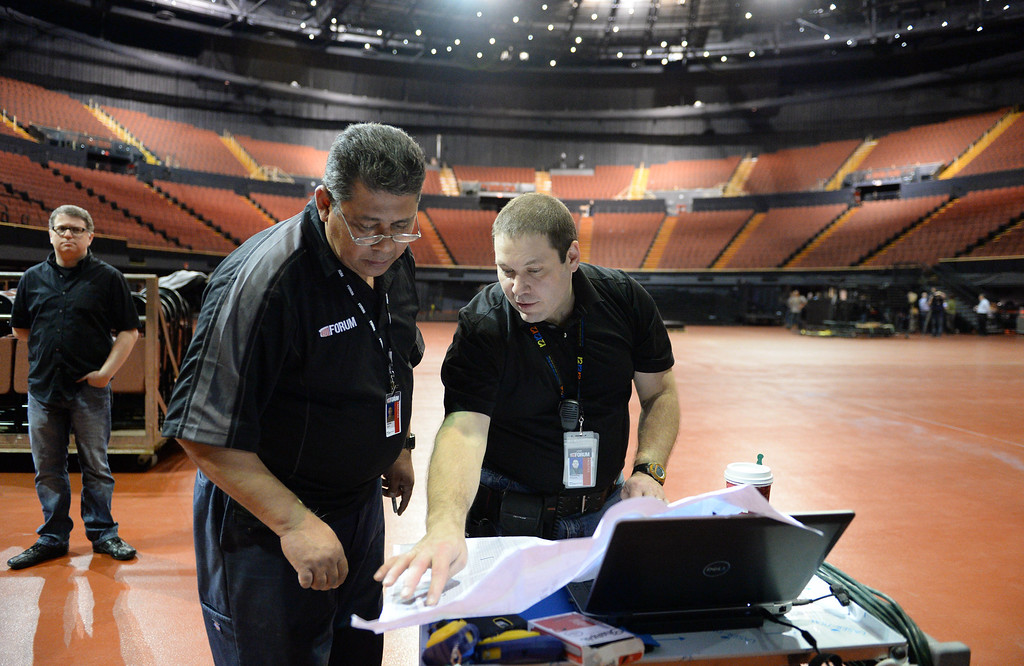 """. The new entertainment venue, the \""""Fabulous\"""" Forum in Inglewood has undergone a $100 million renovation, and is set to host the Eagles concert series starting Jan 15.  VP of Event Production Timothy Parsaca, center, goes over details with Jim Barto, left, as production ramps up for the Eagles 6-night concert run.   (Jan 14, 2014. Photo by Brad Graverson/The Daily Breeze)"""