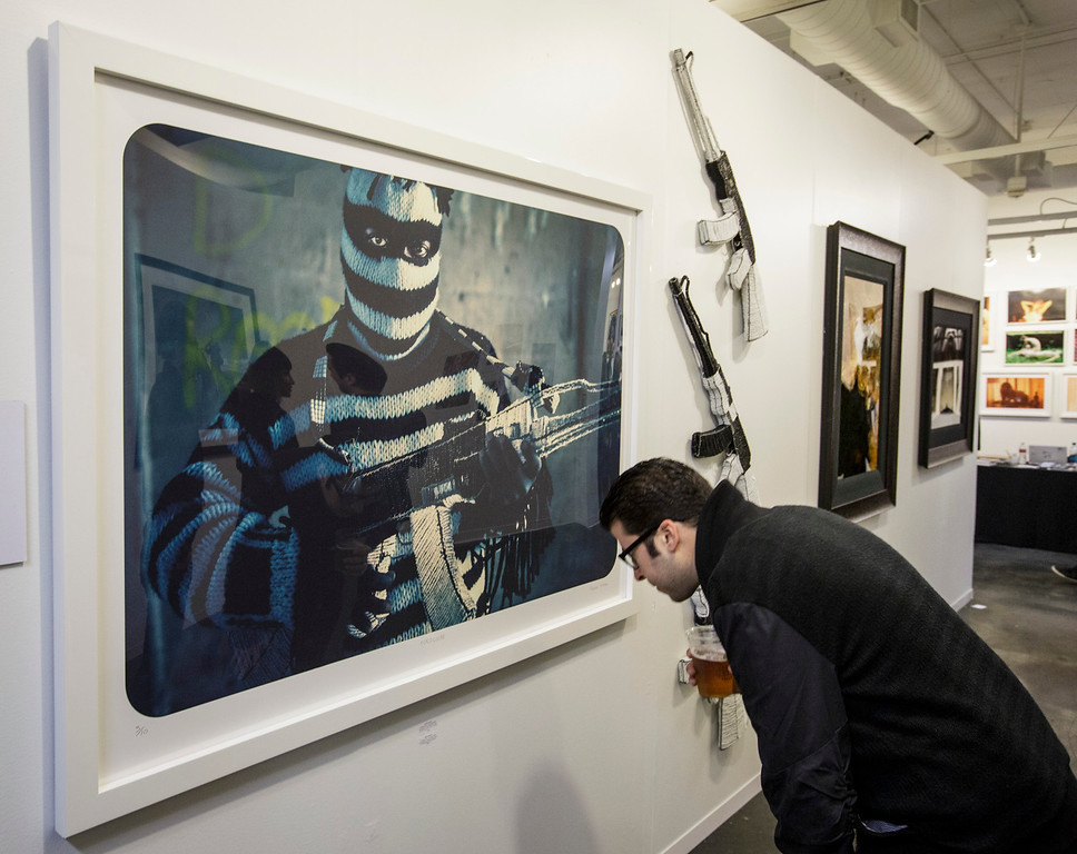 . A visitor views a  photo of a man holding a weapon made of beads by photographer Ralph Ziman  at the photo la opening party held at The REEF/LA Mart in Los Angeles, CA. January 15, 2015.  Photo by David Sprague/Special to the Daily News