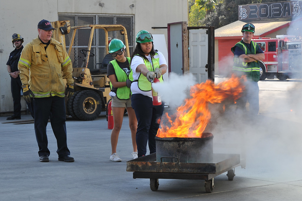 . Poly High School student, Vivian Munoz, left, and Myleenah Gray extinguish a fire at Long Beach Fire Department station 17 where the city\'s first Teen C.E.R.T. Class graduated on Saturday. The 36 students completed a natural disaster scenario of a 7.2 earthquake and aftershocks in the city. They put out fires, freed victims and even delivered a baby in the afternoon of training. Long Beach January 18, 2014. (Photo by Brittany Murray / Press Telegram)