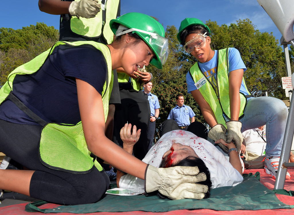 . Poly High School student, Sara De Los Reyes, left, and Laura Holley tend to a staged pregnant victim at Long Beach Fire Department station 17 where the city\'s first Teen C.E.R.T. Class graduated on Saturday. The 36 students completed a natural disaster scenario of a 7.2 earthquake and aftershocks in the city. They put out fires, freed victims and even delivered a baby in the afternoon of training. Long Beach January 18, 2014. (Photo by Brittany Murray / Press Telegram)