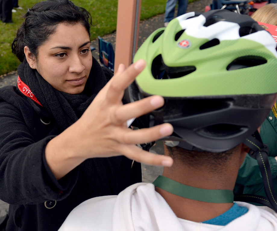 . Amanda Helguera helps a student with his bike helmet as the Long Beach Fire Honoraries have spent months raising money to donate 22 bikes to local high school students, working in conjunction with the Long Beach Unified School District as they give out the bikes in Long Beach, CA. December 3, 2013. The  Long Beach Unified School District have picked 11 boys and 11 girls who they feel are deserving of receiving a new bike for the Christmas season, helmets and locks are included. (Thomas R. Cordova/Press-Telegram/Daily Breeze)
