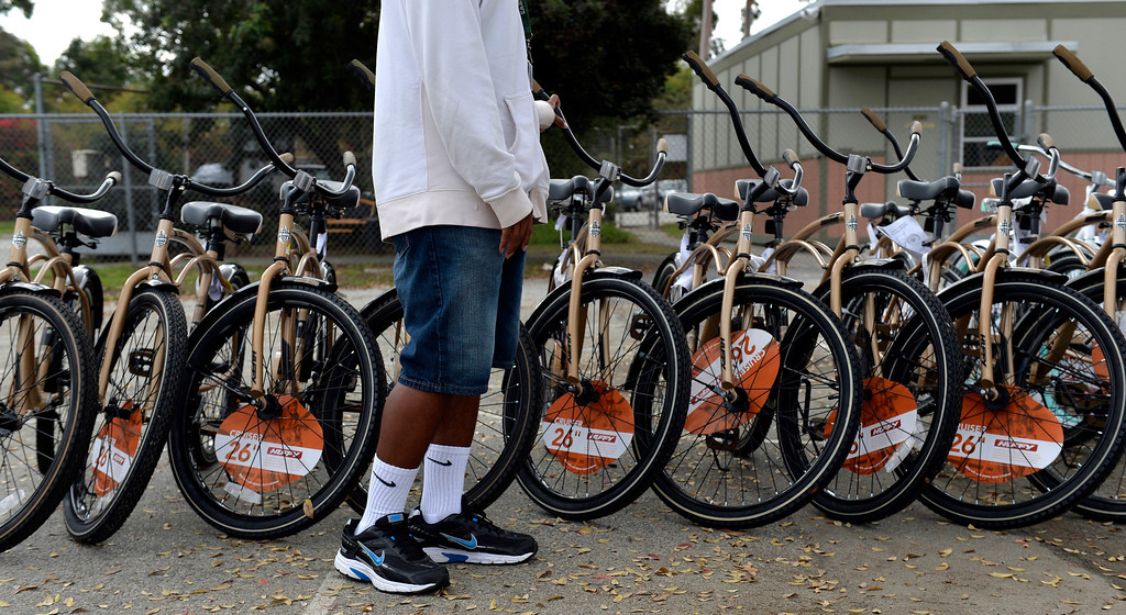 . A student picks out his bike as the Long Beach Fire Honoraries have spent months raising money to donate 22 bikes to local high school students, working in conjunction with the Long Beach Unified School District as they give out the bikes in Long Beach, CA. December 3, 2013. The  Long Beach Unified School District have picked 11 boys and 11 girls who they feel are deserving of receiving a new bike for the Christmas season, helmets and locks are included. (Thomas R. Cordova/Press-Telegram/Daily Breeze)