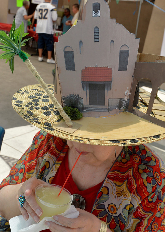 . Maria Teresa Diaz enjoys her cold drink as she sports her homemade hat that is replica of St. Isidore Church during a Cinco de Mayo Fiesta at St. Isidore Historical Plaza in Los Alamitos, CA. Sunday May 4, 2014.The celebration had folklorico dancers, a choir and a Mariachi band. In 1926, this historic landmark was built. It was named St. Isidore after the patron Saint of laborers and farm workers. St. Isidore was celebrating more than Cinco de Mayo, as of last week it pasted escrow so all the money raised during the event go\'s to preserving the plaza. The once Catholic church is now non-denominational church. (Thomas R. Cordova-Daily Breeze/Press-Telegram)