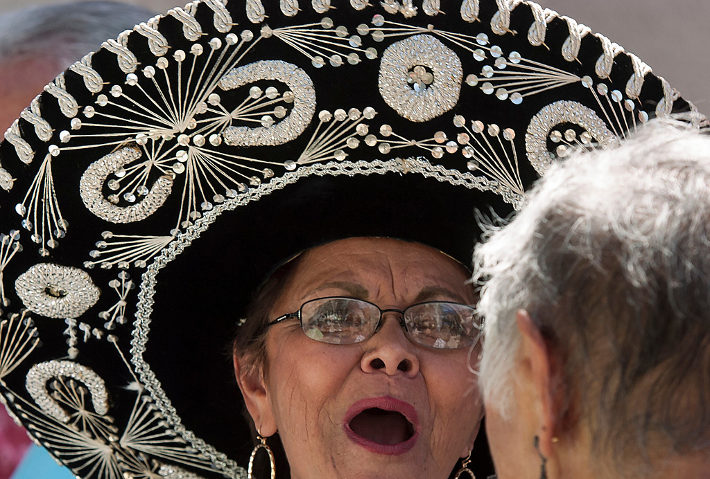 . Esther Murphy wheres a sombrero as she talks to friends at a Cinco de Mayo Fiesta at St. Isidore Historical Plaza in Los Alamitos, CA. Sunday May 4, 2014.The celebration had folklorico dancers, a choir and a Mariachi band. In 1926, this historic landmark was built. It was named St. Isidore after the patron Saint of laborers and farm workers. St. Isidore was celebrating more than Cinco de Mayo, as of last week it pasted escrow so all the money raised during the event go\'s to preserving the plaza. The once Catholic church is now non-denominational church. (Thomas R. Cordova-Daily Breeze/Press-Telegram)