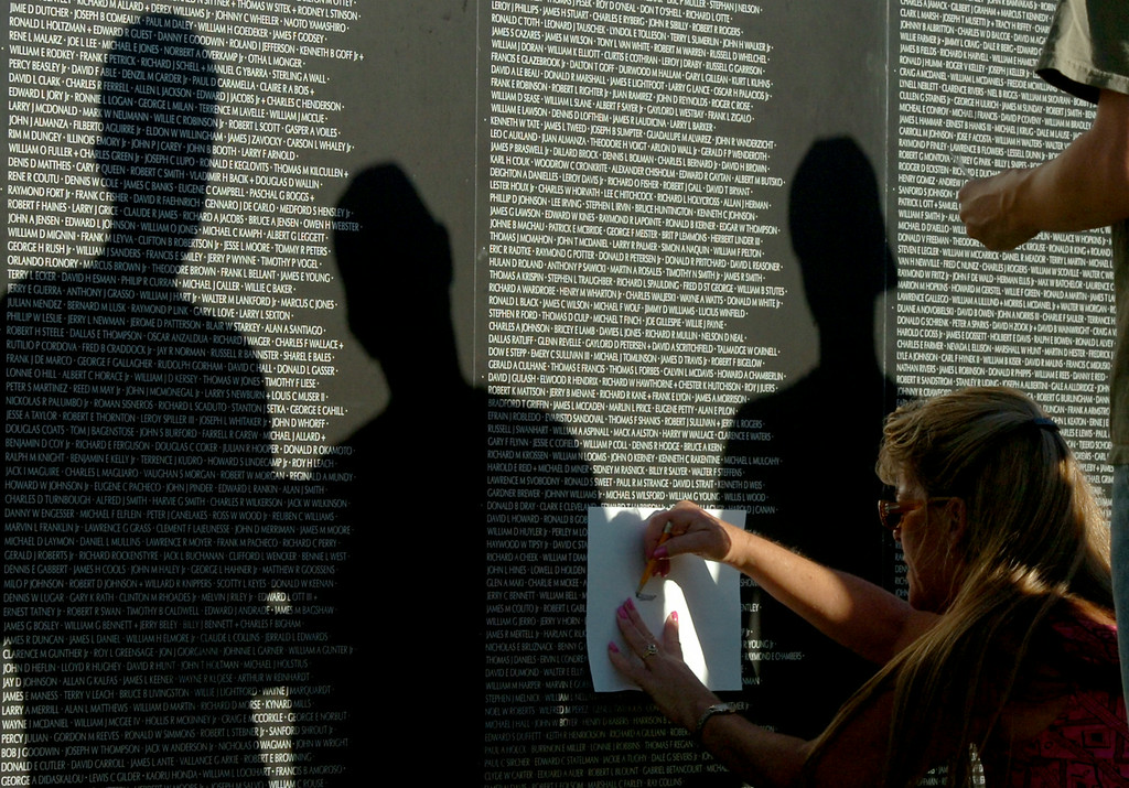 . Tracey Willett, of Lakewood, rubs out her husbands uncles name as her family stands around her at the traveling Vietnam Veterans Memorial Wall on display in Lakewood\'s Mayfair Park in Lakewood CA. Thursday August 14, 2014. The traveling wall is 80 percent-sized replica is 360-feet long. (Thomas R. Cordova-Daily Breeze/Press-Telegram)