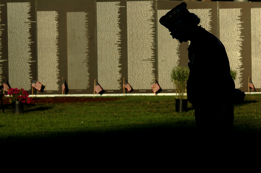 . Vietnam Veteran Mike Laughlin lowers his head during a ceremony in front of the traveling Vietnam Veterans Memorial Wall which is on display at Lakewood\'s Mayfair Park in Lakewood CA. Thursday August 14, 2014. The traveling wall is 80 percent-sized replica is 360-feet long. (Thomas R. Cordova-Daily Breeze/Press-Telegram)