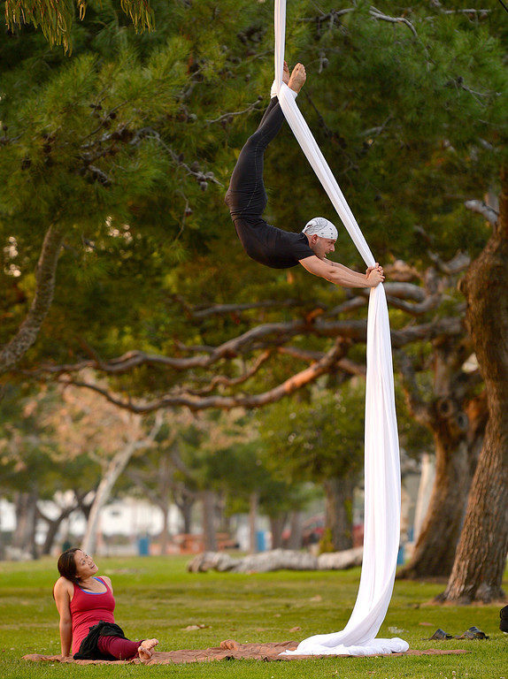 . Lisa La, of Seal Beach, watches Vincent Tedino, of Long Beach, as he does his aerial silks workout at Mother Beach in Long Beach, CA. December 18, 2013. The two just enjoy working out on the Aerial Silks at the park. (Thomas R. Cordova/Press-Telegram/Daily Breeze)