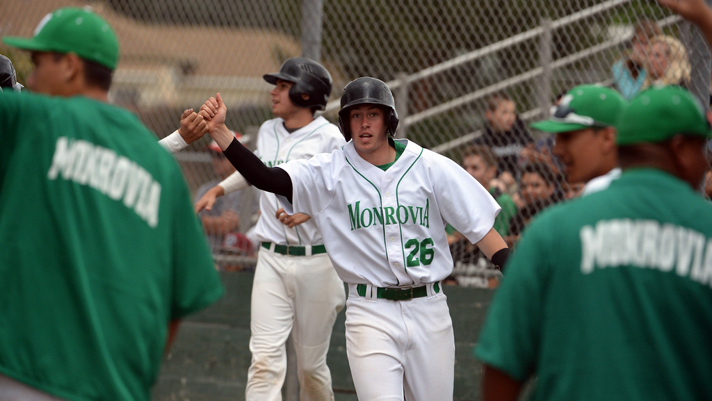 . Monrovia\'s Ben Goettling (26) high fives Fidel Jiorge after scoring on a double by Juan Quinonez (not pictured) against Whittier Christian in the fourth inning of a prep playoff baseball game at Monrovia High School in Monrovia, Calif., on Thursday, May 21, 2015. Monrovia won 6-1.  (Photo by Keith Birmingham/ Pasadena Star-News)