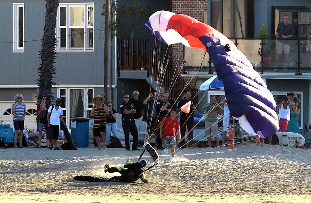 . A parachutist drops from the sky and lands on the Peninsula beach   during Big Bang on the Bay,  a community  block party that took place from 5:30 to 9:30 p.m. at The Boathouse on the Bay.  The party featured live music food and flyovers by parachutists, vintage aircraft and topped off by Fireworks over Alamitos Bay. Long Beach Calif.,  Thursday July 3,  2014.    (Photo by Stephen Carr / Daily Breeze)
