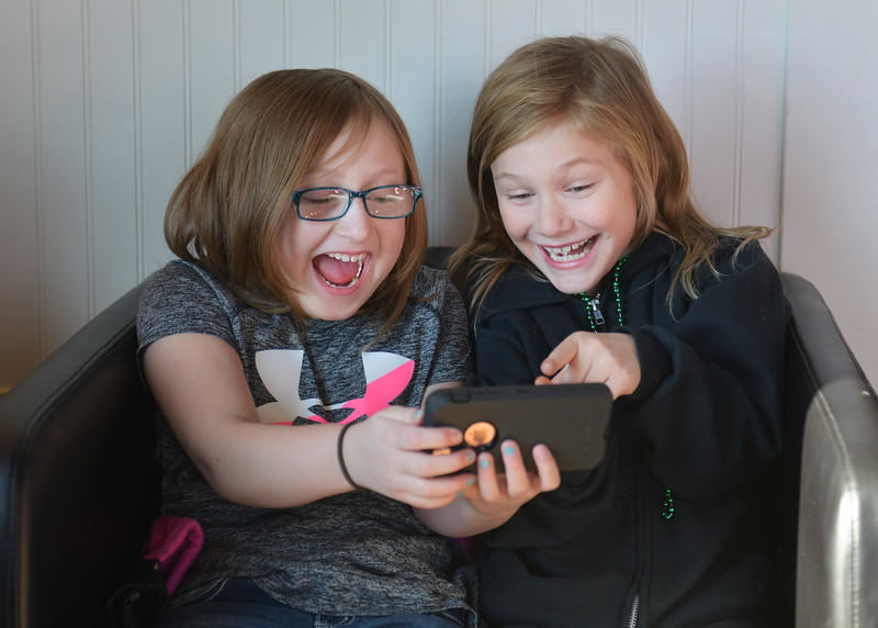 Justin Sheely | The Sheridan Press<br /> Nine-year-old Ariah Couch, left, and Delaney Morel take selfies on a phone as Morel's mother purchases cookies during the 3rd-annual Valentine's Day cookie decorating event at Andi's Coffee House Saturday, Feb. 10, 2018.