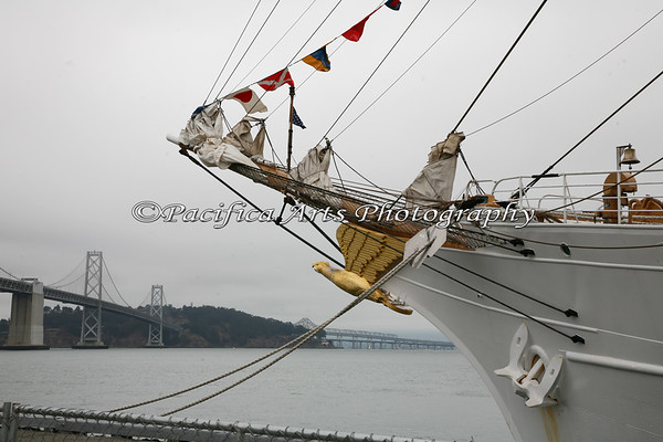 """USCGC Eagle"" - bow of ship, with figurehead of a gold eagle.  San Francisco/Oakland Bay Bridge on left."