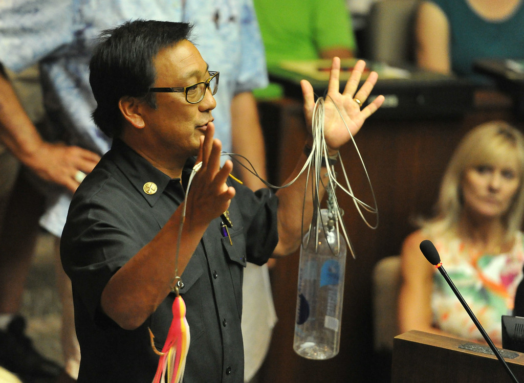 . Terry Yamamoto, Los Angeles County Lifeguard Section Chief, shows a shark hook, rigged to a wire line and plastic water bottle for floatation, that washed up recently after a big swell near 18th Street in Manhattan Beach, during the Manhattan Beach City Council meeting to discuss the possible ban fishing off the pier, in response to the recent shark attack, in Manhattan Beach, CA. on Tuesday July 15, 2014. (Photo by Sean Hiller/ Daily Breeze).