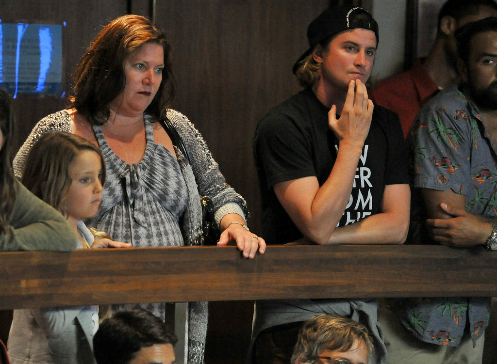 . Pro surfer Alex Gray, center, listens to public comment at the Manhattan Beach City Council meeting, addressing the possible ban on fishing off the pier, after a swimmer was bitten by the great white shark, in Manhattan Beach, CA. on Tuesday July 15, 2014. (Photo by Sean Hiller/ Daily Breeze).