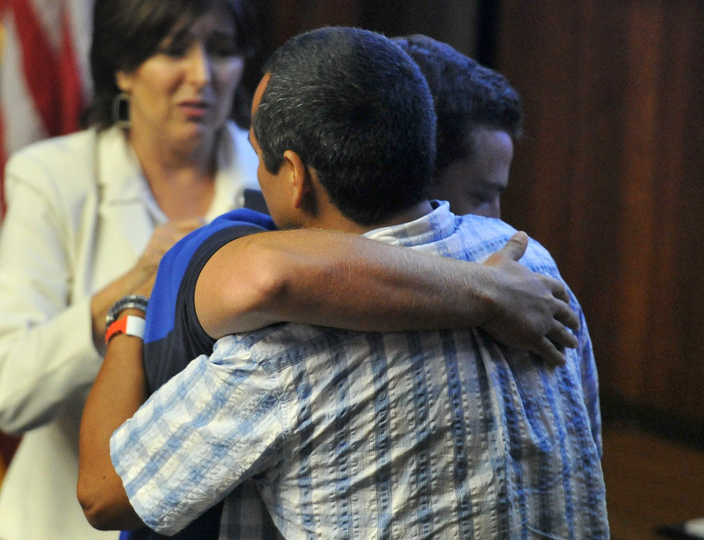 . Shark attack victim Steven Robles, right, get a hug from Ryan Silver, facing the camera, who helped save him from the water, before the Manhattan Beach City Council heard public comment about the possible ban on fishing off the pier after the recent shark attack, in Manhattan Beach, CA. on Tuesday July 15, 2014. (Photo by Sean Hiller/ Daily Breeze).
