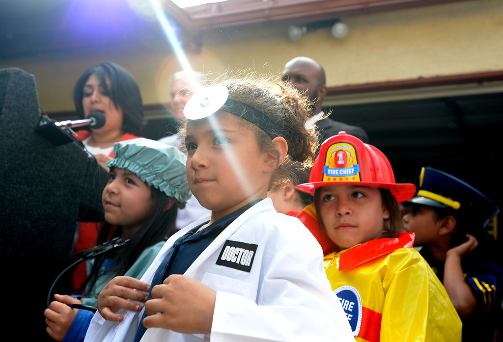 . Pearla Castellanas, left, dressed as a nurse, Eva Flores, 5, dressed as a doctor, center, and Melody Campos, 6, represent the future work force that early learning can provide, at the press conference for the  �Gapbusters� Child Care Bus Tour, that stopped by Ramona�s Day Care in Long Beach, CA. on Tuesday, February 18, 2014. (Photo by Sean Hiller/ Daily Breeze).