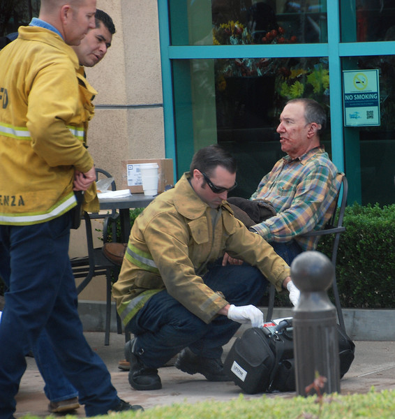 Paramedics tend to the good Samaritan who was stabbed Monday, Nov. 21, 2016, at the Gelson's Market in Valley Village. The man, who was described as being in his 70s, was stabbed when he tried to protect a security guard who was being charged by a shoplifting suspect's boyfriend, according to reports from the scene. (Photo by Mike Meadows/Special to the Los Angeles Daily News)