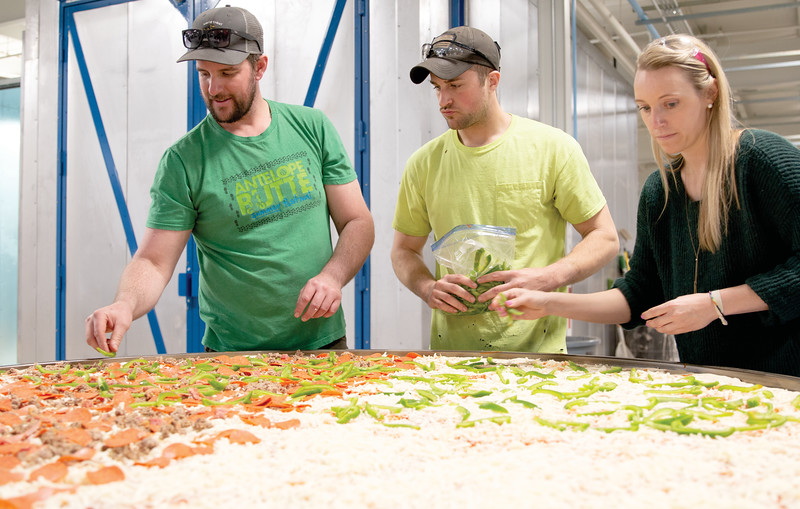 """Matthew Gaston   The Sheridan Press<br>EMIT Technologies staffers, from left, """"Papa"""" Cole Yada, Skylar Britton and Darcy Sengewald begin the process of topping a massive 6-foot diameter pizza Friday, March 22, 2019."""