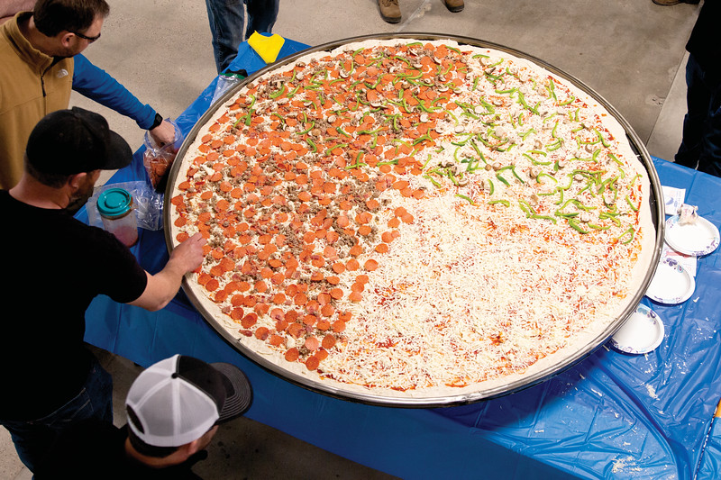 Matthew Gaston   The Sheridan Press<br>The massive pizza is almost ready to for baking in EMIT's brand new powder coating oven Friday, March 22, 2019. Travis Hetland, the owner of Hetty's Pizza, lent his expertise in preparing this monstrous pie.