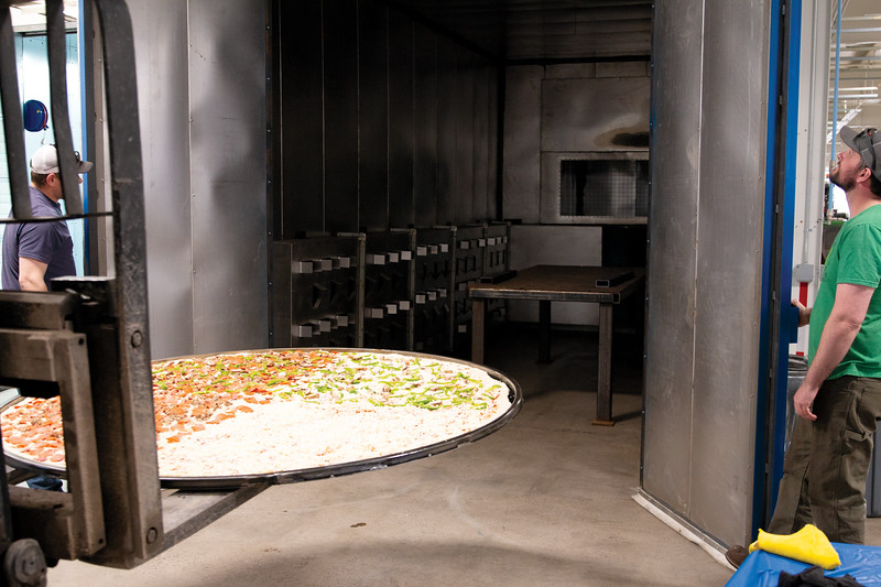 Matthew Gaston   The Sheridan Press<br>This juggernaut of a pizza made by Travis Hetland from Hetty's Pizza is so large a forklift was required to place it in the new powder coat oven at EMIT Technologies for baking Friday, March 22, 2019.
