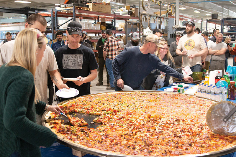Matthew Gaston   The Sheridan Press<br>The staff at EMIT Technologies lines up to sample the largest pizza Sheridan has likely seen. It was baked in the company's new powder coat oven by Hetty's Travis Hetland Friday, March 22, 2019.